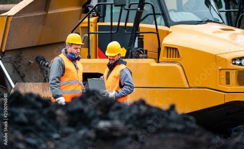 Fotografia Arbeiter im Tagebau schauen auf einen Plan