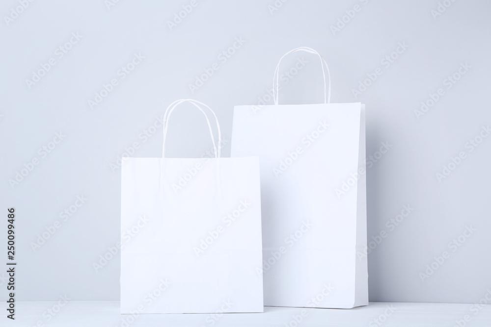 Fototapeta White shopping bags on grey background