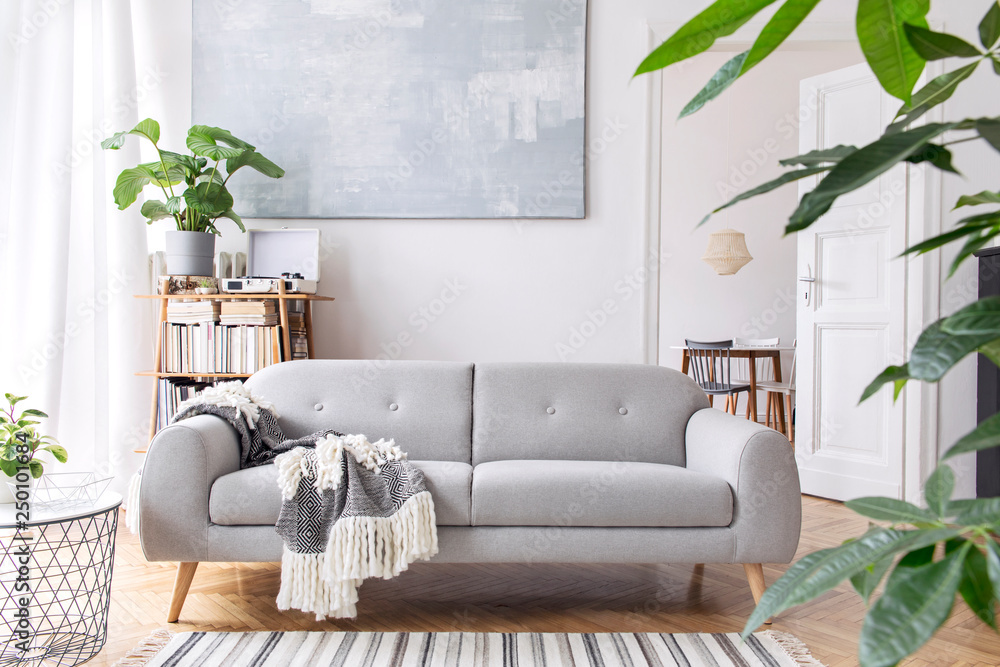 Fototapety, obrazy: Stylish scandianvian decor of living room with design sofa with elegant blanket, coffee table, plants and bookstand. Brown wooden parquet. Concept of minimalistic interior in nice apartment.