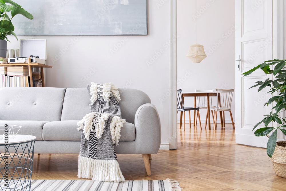 Fototapety, obrazy: Modern scandianvian living room with design sofa with elegant blanket, coffee table and bookstand on the white wall. Brown wooden parquet. Concept of minimalistic interior. View on dining room.