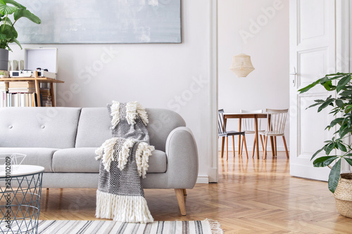 Fotografía  Modern scandianvian living room with design sofa with elegant blanket, coffee table and bookstand on the white wall