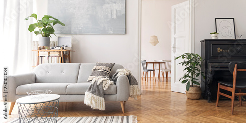 Pinturas sobre lienzo  Modern scandianvian decor of living room with design sofa, elegant blanket, coffee table, plants and bookstand on the white wall