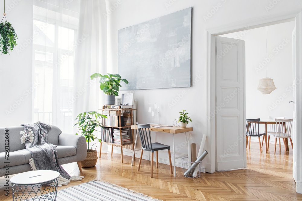 Fototapeta Stylish scandinavian open space with design furniture, plants, bamboo bookstand and wooden desk. Brown wooden parquet. Abstract painting. Modern decor of bright room next to dining room.