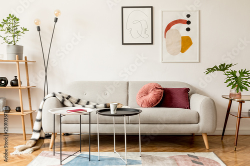 Fotografia, Obraz  Stylish retro and vintage interior of sitting room with design sofa, tables, lamp, bookstand, blanket and mock up poster frame gallery on the white walls