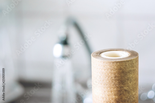 Photo  Dirty, brown, used water filter cartridges on background of the sink and tap wit
