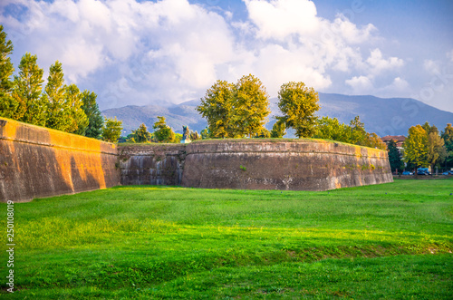 Foto auf AluDibond Grun Defensive brick city wall, grass green lawn, trees and Tuscany hills and mountains with beautiful cloudy evening sky background, Lucca, Italy