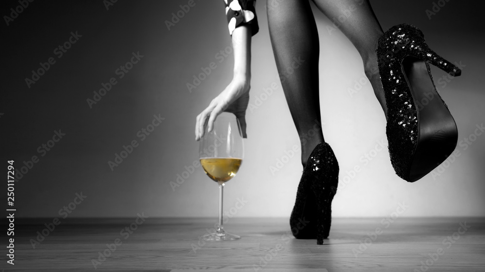 Fototapety, obrazy:  Beautiful girl legs and a glass of alcoholic beverage, black white photo, golden champagne in a glass