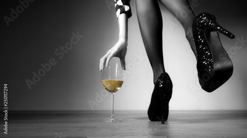 Beautiful girl legs and a glass of alcoholic beverage, black white photo, golden champagne in a glass - 250117294