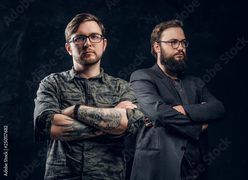 Photo  Two professional computer technicians posing with confident look in a studio wit