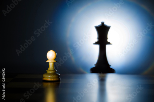 Fotografie, Obraz  A pawn on a chessboard looks at its shadow of the future queen