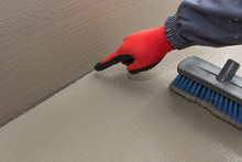 The Worker Shows The Space Between The Wall And The Floor, Additional Waterproofing Is Needed
