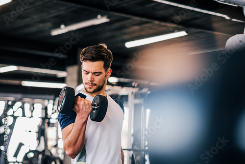 Fotografia  Young man in sportswear exercising with weights.