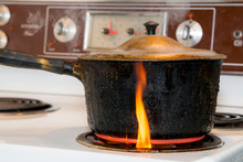 An Old, Covered, Charred, Blackened Pot Burning On A Burner On An Electric Stove. The Small Flame Is On The Outside Of The Pot Rising From The Burner.