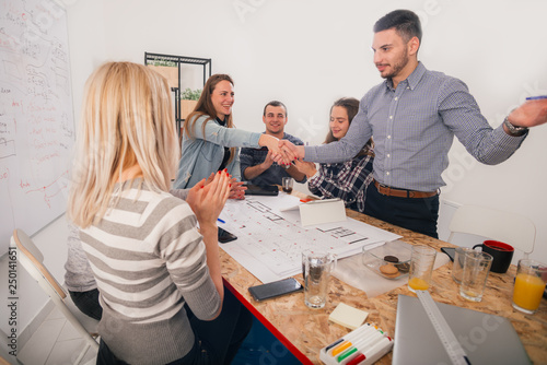 Fototapety, obrazy: A group of young entrepreneurs discussing their next project at a meeting pointing at the blueprint which is at the middle of the table.