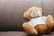 A small plush teddy bear measures a fever with an electronic thermometer. Medicine and health concept. Thermometer placed under the armpit of a teddy bear. Disease, flu and cold.