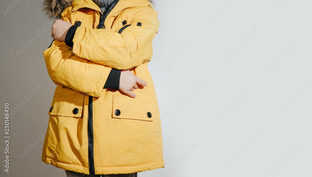 Fototapeta Front view of Child dressed in a yellow winter jacket with fur on the hood. The concept of dressing the child on winter days, the upcoming frosts. Children's fashion concept, clothes stores.