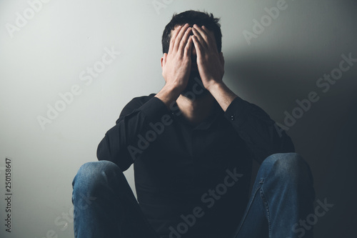 Photo sad man sitting hand in face