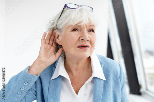 Come again please? Attractive mature woman wearing blue jacket and spectacles on her head eavesdropping Fototapeta