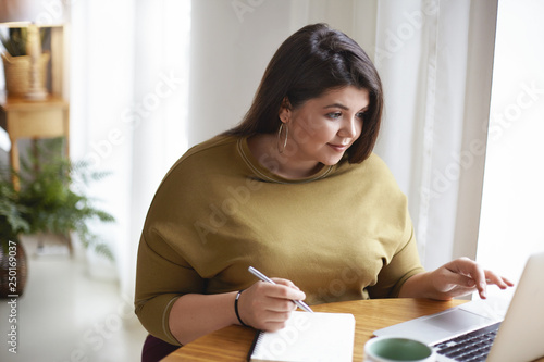 Photo Indoor shot of overweight plus size beautiful young brunette lady in stylish clo