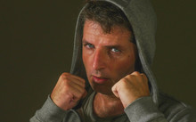 Young Attractive And Fierce Looking Man Wearing Hoodie Posing In Aggressive Fighter Stance Isolated On Dark Background In Sport And Fitness Or Threatening Thug