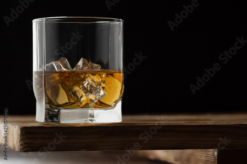 Foto op Canvas Alcohol Glass of whiskey with ice cubes on a wooden table and dark background.