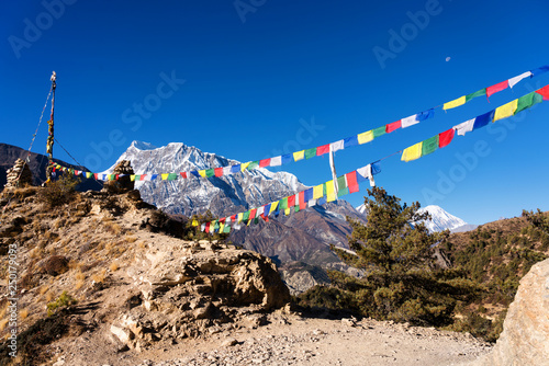 Panoramic views on a popular tourist destination trail in Nepal - Annapurna Circuit Trail. Way to base camp and Thorong La or Thorung La pass. View with colorful buddhist flags flapping on the wind.