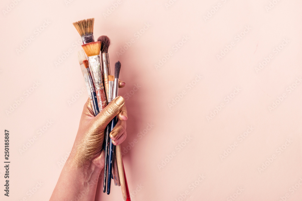 Fototapety, obrazy: Artist golden hand with set of brushes on pale pink background