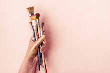 Artist Golden Hand With Set Of Brushes On Pale Pink Background