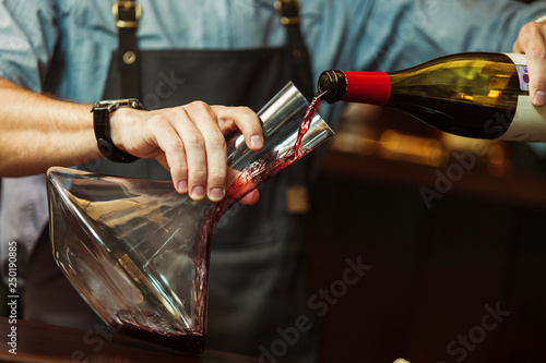 Sommelier pouring red wine into carafe to make perfect color Canvas Print