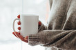 Leinwandbild Motiv Close up of women's hands holding white mug with blank copy space scree for your advertising text message or promotional content, sweet coffee or tea.