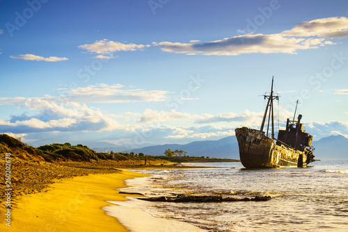 Tuinposter Schip Rusty broken shipwreck on sea shore