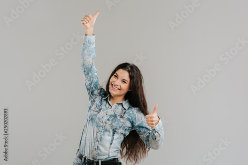 Fotografía  a happy woman raising her hand up, is showing Ok sign, isolated on gray background