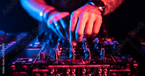 Close up of DJ hands controlling a music table in a night club. Tablou Canvas