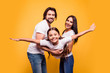 Leinwanddruck Bild - Portrait of nice sweet lovely attractive cheerful cheery people dad daddy mom mommy mum holding in hands carrying pre-teen girl isolated over shine vivid pastel yellow background