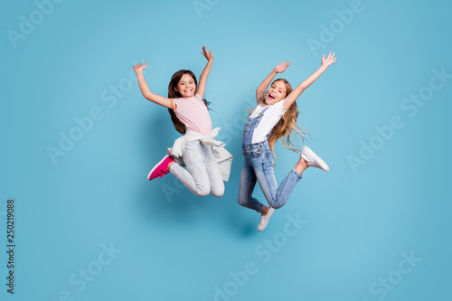 Obraz Full length body size view of two people nice-looking crazy lovely attractive cheerful carefree straight-haired pre-teen girls having fun great weekend time overjoy isolated over blue pastel - fototapety do salonu