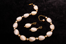 A Beige Beads And Earrings With Gold Inserts On A Chain