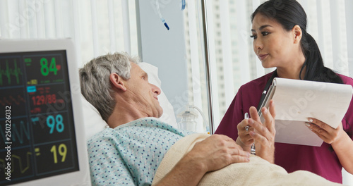 Valokuva  Asian woman doctor talking with senior Caucasian male patient lying in hospital bed