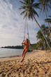 Young girl in a red swimsuit on the beach swinging on a swing