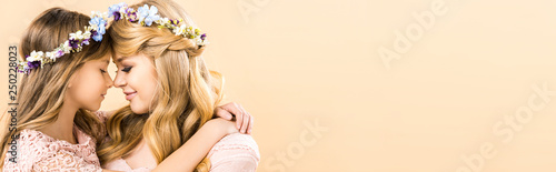 Fotografie, Obraz  beautiful woman and adorable child in colorful floral wreaths hugging face to fa
