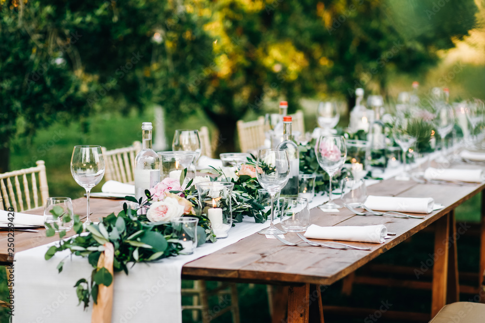 Fototapeta Floral garland of eucalyptus and pink flowers lies on the table for wedding reception. Italian dinner
