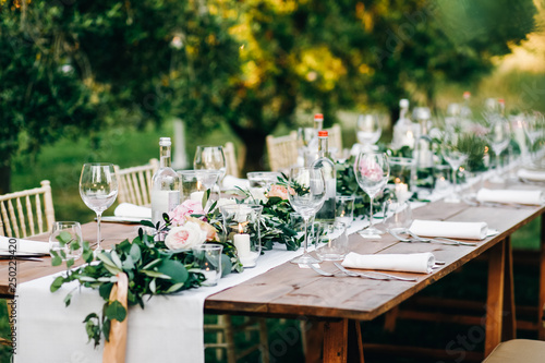 Floral garland of eucalyptus and pink flowers lies on the table for wedding reception Wallpaper Mural