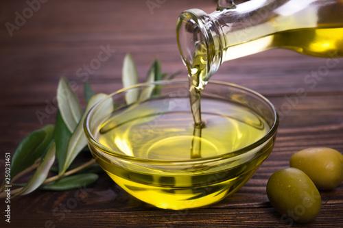 Obraz na plátně Bowl with olive oil on wooden table