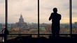 silhouette of a man trying to take a photo at the Apartment or office with panoramic windows and a beautiful view of the city of Moscow. Long shot.