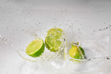 Ripe cut lime with water splash on white background