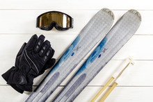 Overhead View Of Ski Accessories Placed On Rustic White Wooden Table.