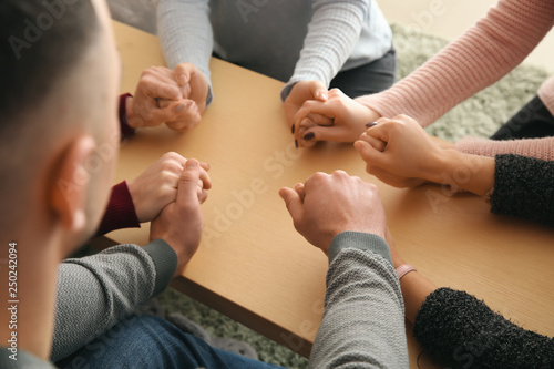 Group of people praying together indoors Canvas Print