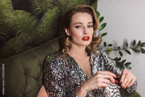 Fotografie, Tablou Young gorgeous actress with wavy hairstyle and red lips in sequins dress sitting