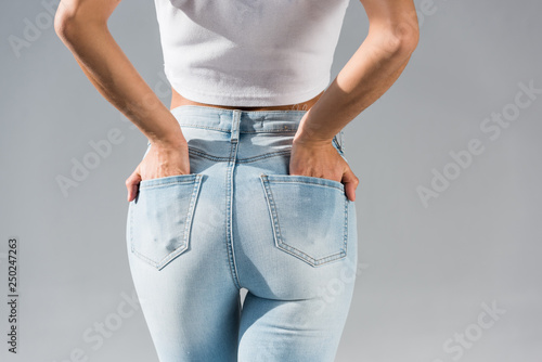 Obraz na plátně  Cropped view of young woman in jeans with hands in pockets isolated on grey