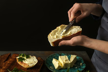 Woman Spreading Tasty Bread With Butter At Table