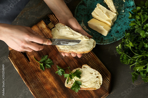 Fototapeta Woman spreading tasty bread with butter at table obraz